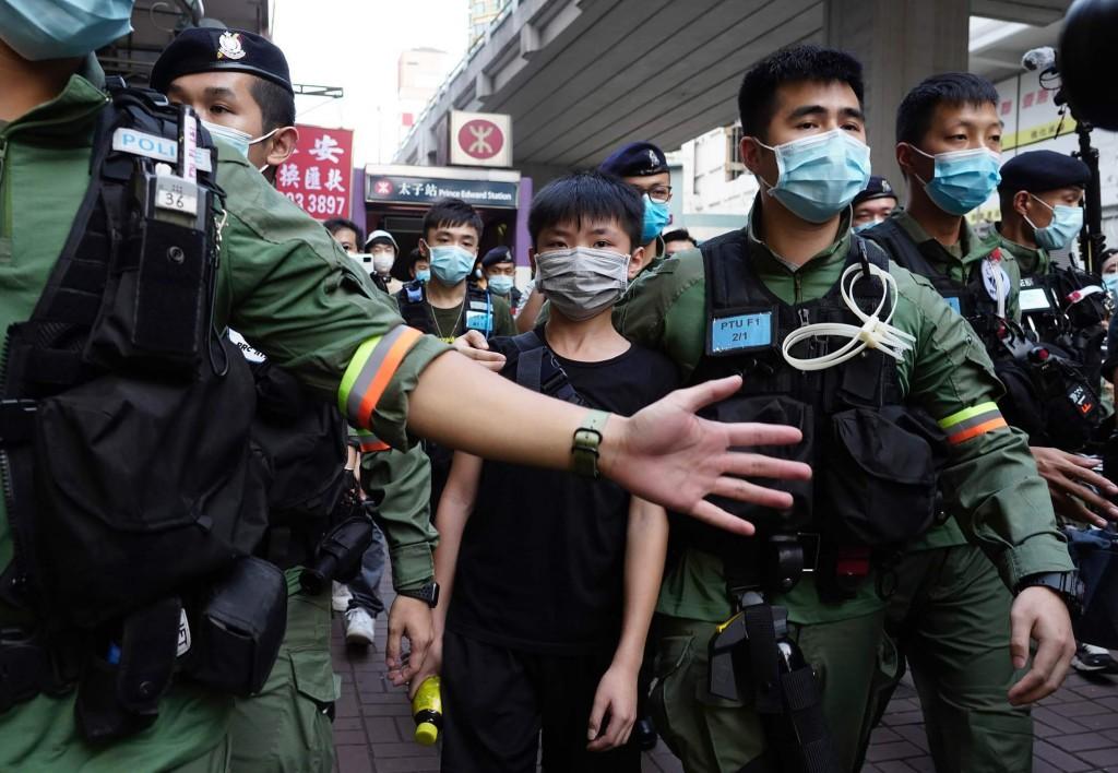 今年8月31日香港一名小男孩在行經一人潮聚集獻花紀念港警施暴周年的車站時,突遭警方逮捕押送至警車,但隨後又獲釋放(美聯社圖片)