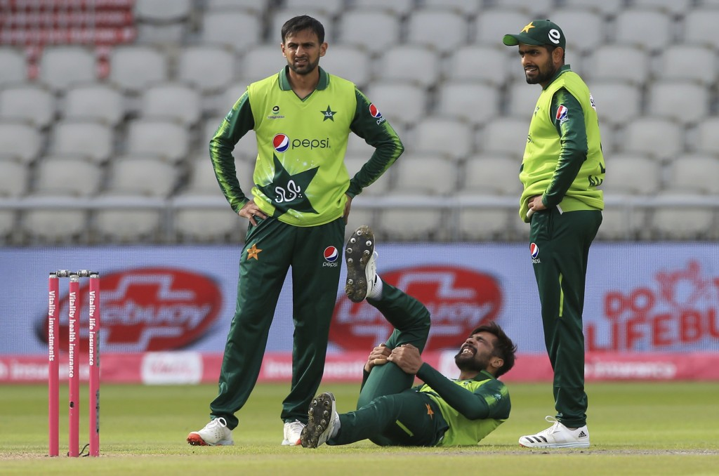 Pakistan's Mohammad Amir, center, reacts in pain after bowling a delivery during the second Twenty20 cricket match between England and Pakistan, at Ol...
