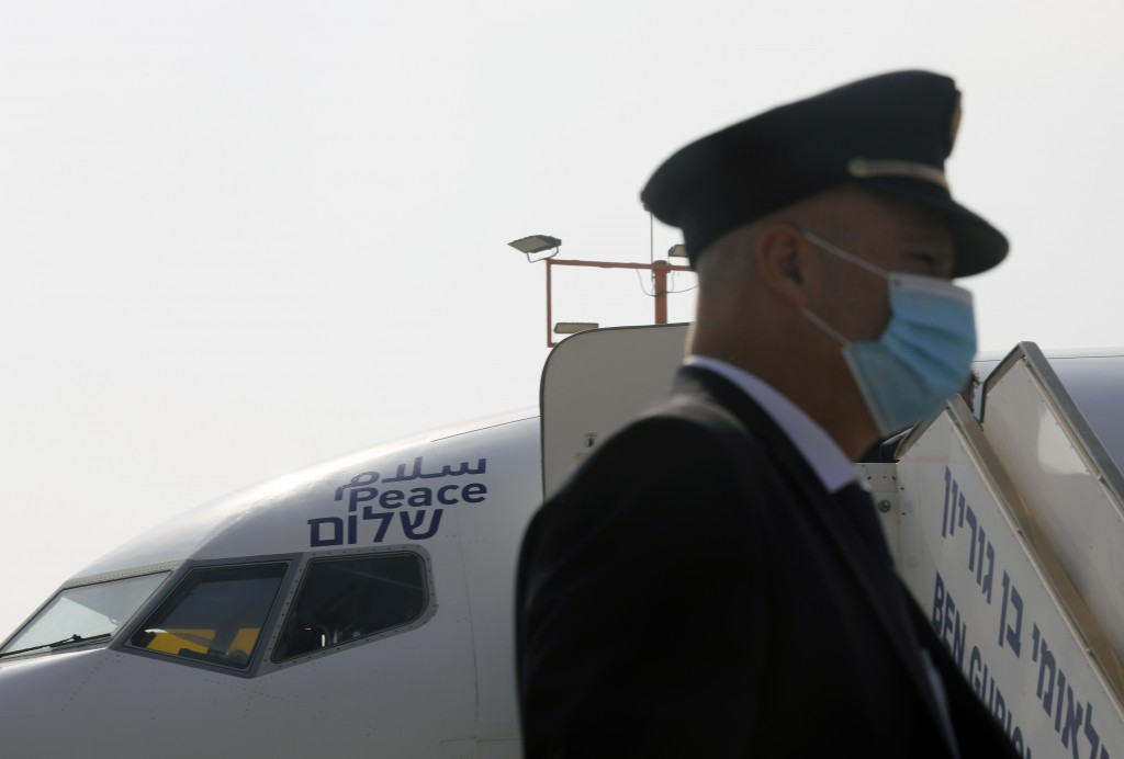 """A flight crew member stands in front of the Israeli flag carrier El Al's airliner bearing the Arabic, English and Hebrew word for """"peace"""" and which wi..."""