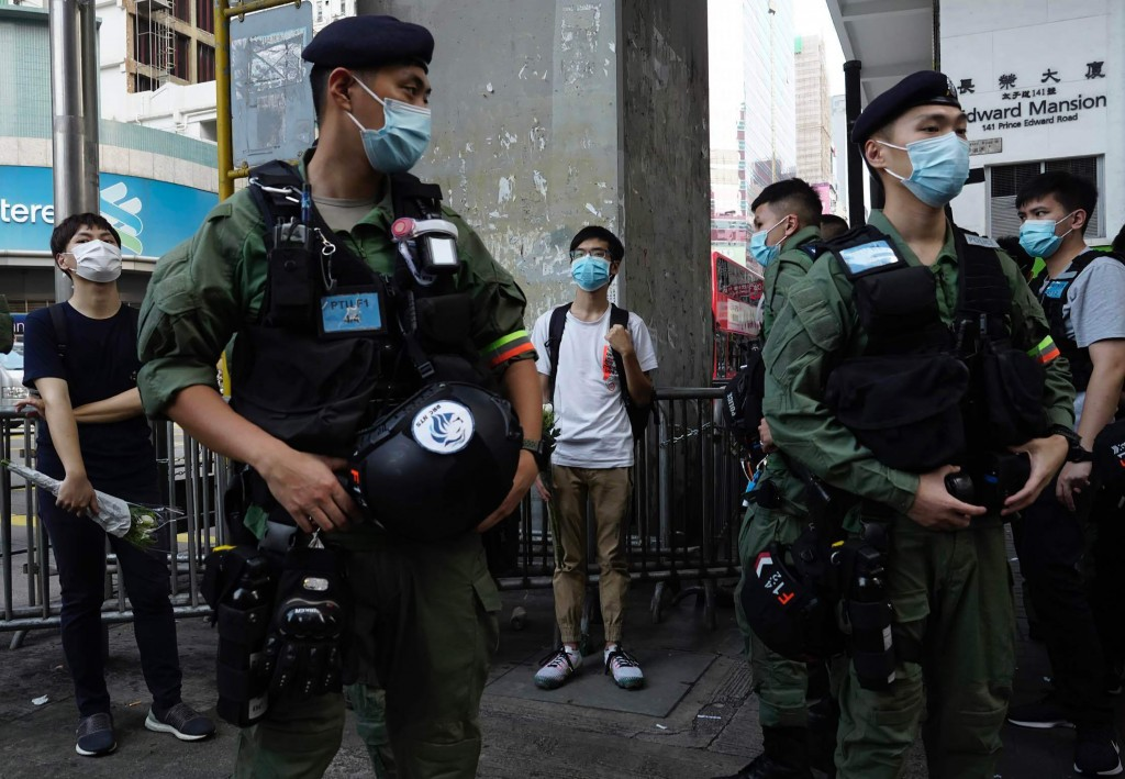 People holding flowers are questioned by police officers outside the Prince Edward subway station in Hong Kong Monday, Aug. 31, 2020. Aug. 31 is the f...