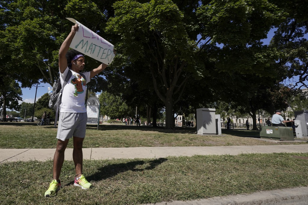 Stan Easley holds up a Black Lives Matter sign at a Blue Lives Matter rally Sunday, Aug. 30, 2020, in Kenosha, Wis. (AP Photo/Morry Gash)