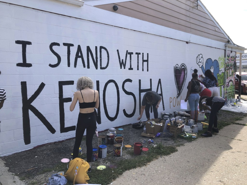 """Volunteers paint murals on boarded-up businesses in Kenosha, Wis., on Sunday, Aug. 30, 2020, at an """"Uptown Revival."""" The event was meant to gather don..."""