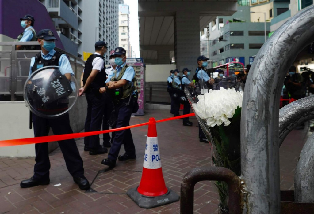 White flowers are placed against police officers outside the Prince Edward subway station in Hong Kong Monday, Aug. 31, 2020. Aug. 31 is the first ann...
