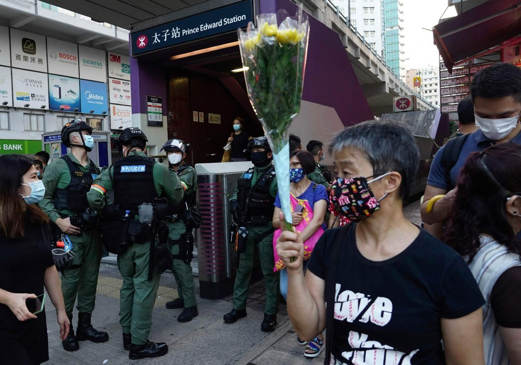 A woman holds flowers outside the Prince Edward subway station in Hong Kong Monday, Aug. 31, 2020. Aug. 31 is the first anniversary of police raid on ...