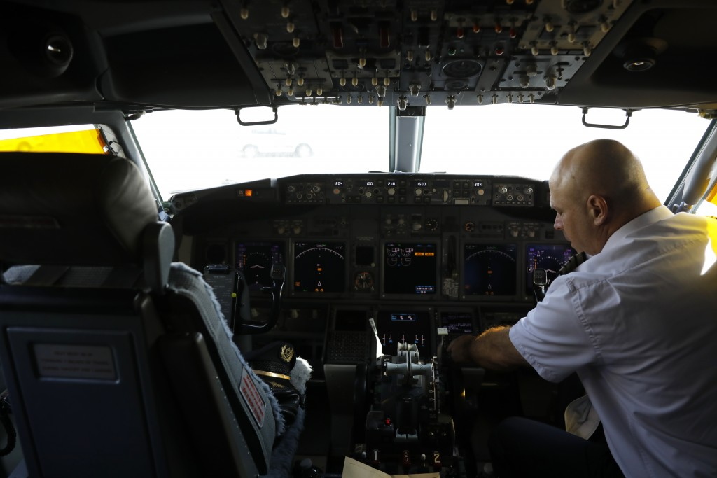 A member of the flight crew sits in the cockpit of the Israeli flag carrier El Al's airliner which will carry Israeli and U.S. delegations to Abu Dhab...