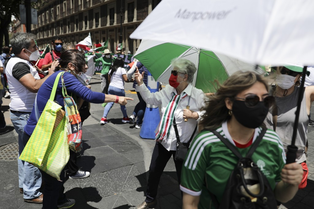 A woman in favor of Mexican President Andres Manuel Lopez Obrador, left, and another one against, argue during a protest demanding the resignation of ...
