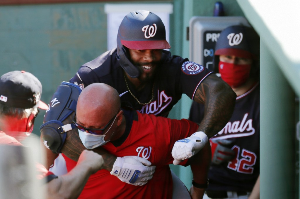 Washington Nationals' Eric Thames, top, celebrates his solo home run during the fifth inning of a baseball game against the Boston Red Sox, Sunday, Au...