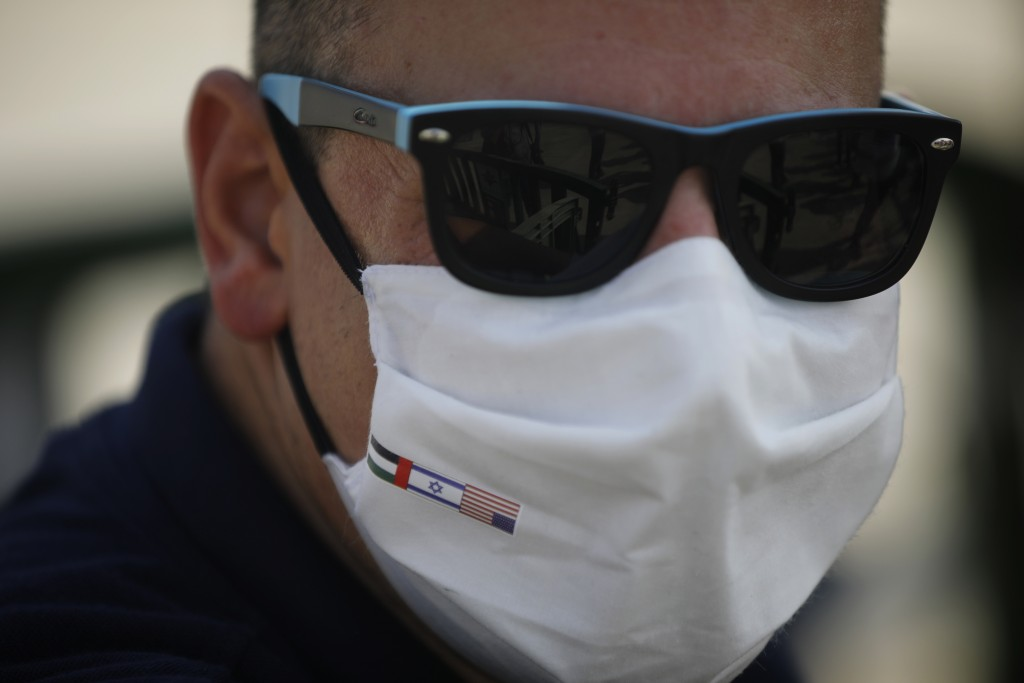 A man wearing a protective face mask with the national flags of America, Israel and United Arab Emirates looks on next to the Israeli flag carrier El ...