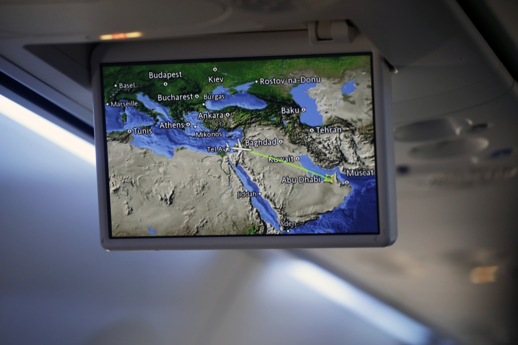 An overhead screen displays a map showing the flight route of an El Al plane from Israel en route to Abu Dhabi, United Arab Emirates, Monday, Aug. 31,...