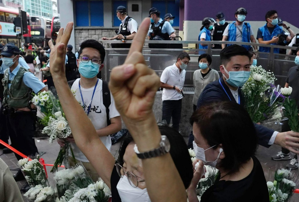 "A protester gestures with five fingers, signifying the ""Five demands and not one less"" outside the Prince Edward subway station in Hong Kong Monday, A..."