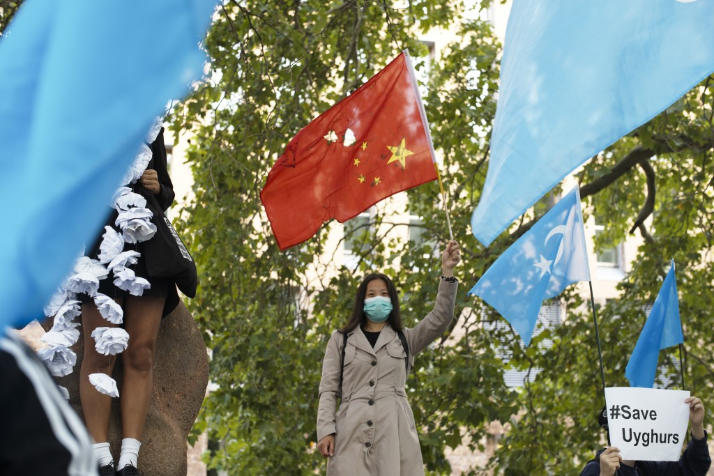 A woman with a partly destroyed Chinese flag stand between demonstrators with Uyghur flags as she attends a protest during the visit of Chinese Foreig...