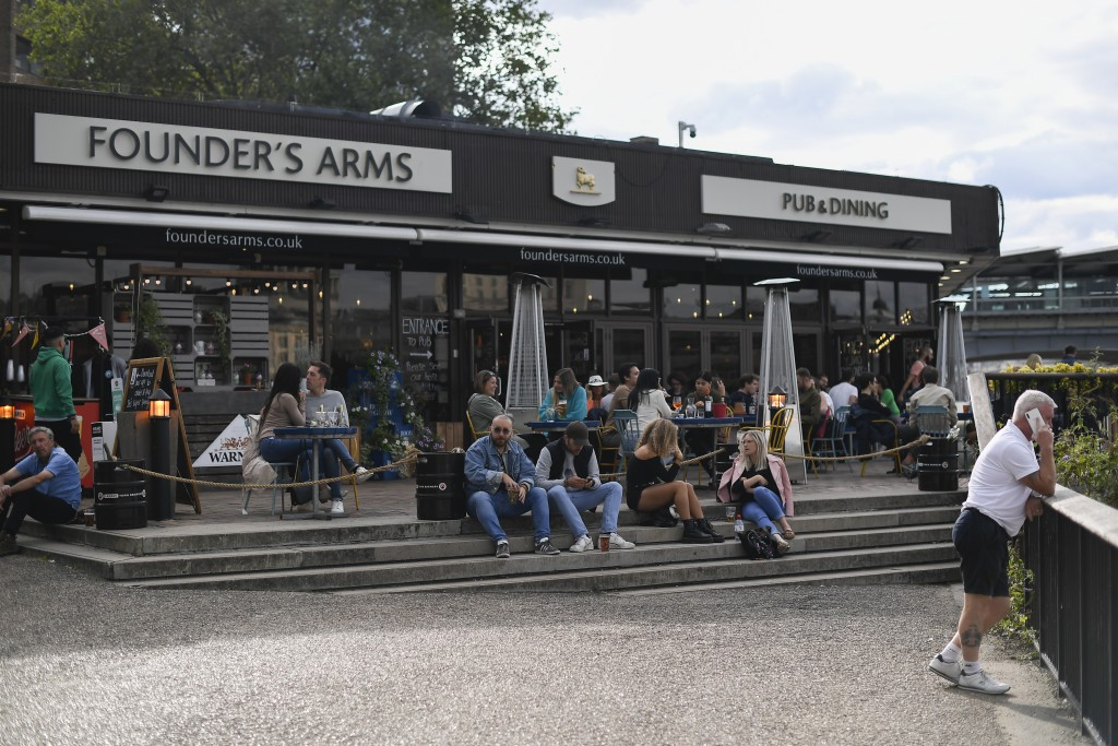People sit outside a pub on the south bank of river Thames in London, Monday, Aug. 31, 2020. Today is the last day of the 'Eat out to help out' scheme...