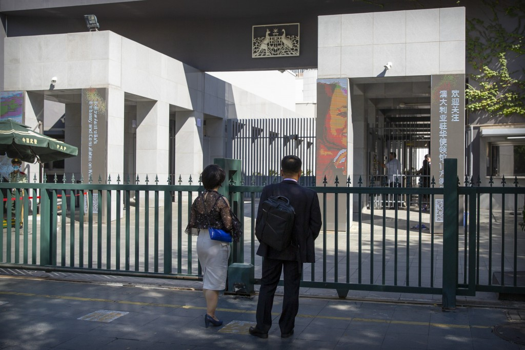 People stand at the gates of the Australian Embassy in Beijing, Tuesday, Sept. 1, 2020. Australia's government says a Chinese-born Australian journali...