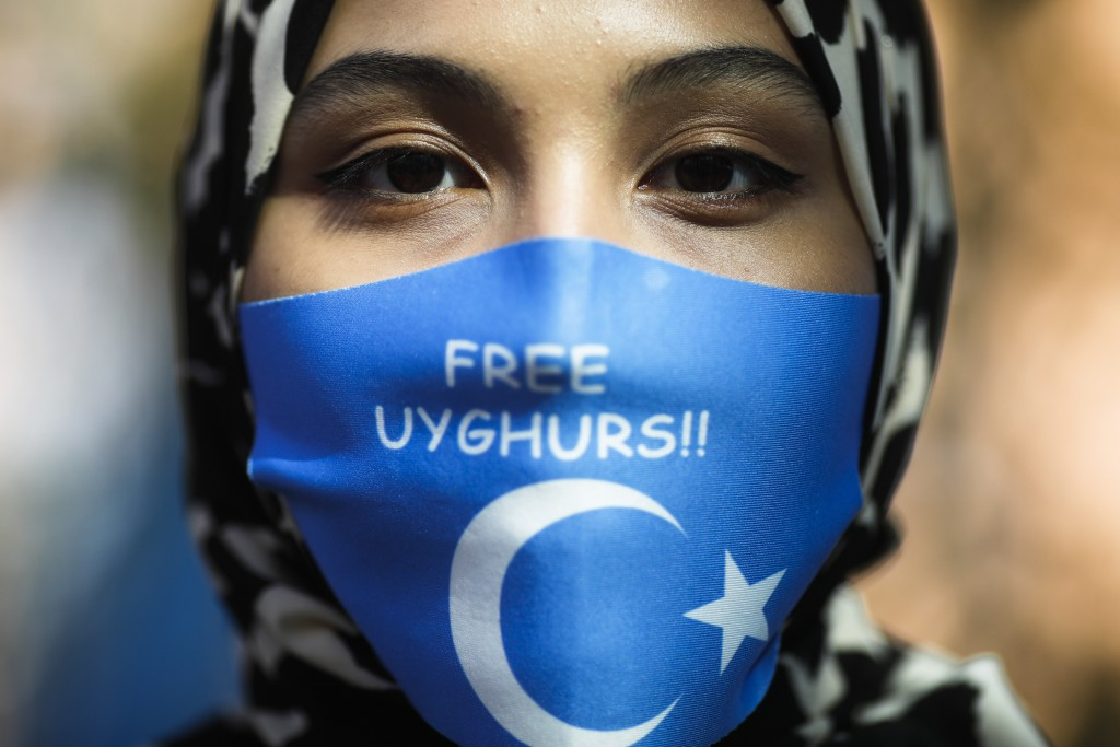 A woman wears a face mask reading 'Free Uyghurs' as she attends a protest during the visit of Chinese Foreign Minister Wang Yi in Berlin, Germany, Tue...