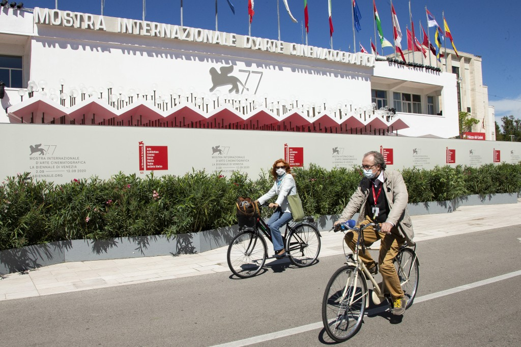 Festival attendees cycle in front of the main cinema ahead of the start of the 77th edition of the Venice Film Festival in Venice, Italy, Tuesday, Sep...