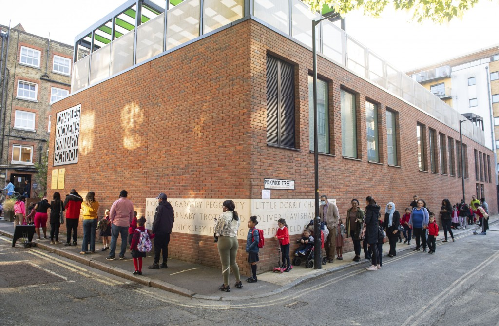 Pupils and parents queue on the first day back to school at Charles Dickens Primary School in London, Tuesday Sept. 1, 2020. Hundreds of thousands of ...