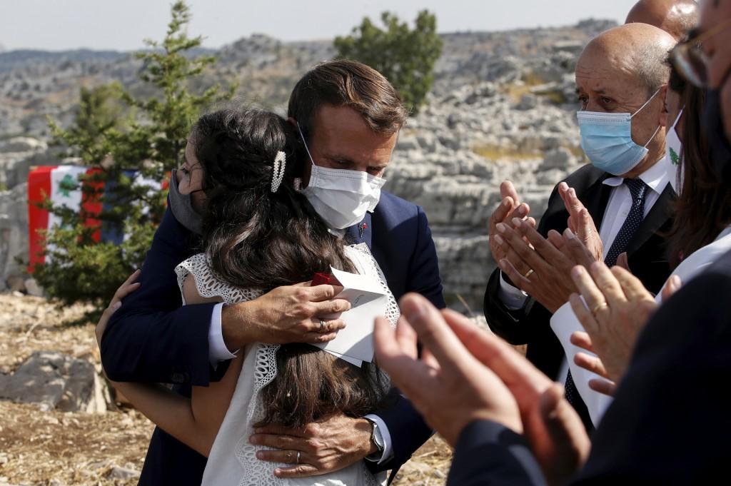 French President Emmanuel Macron hugs blast victim Tamara Tayah after planting a cedar with members of the NGO Jouzour Loubnan in Jaj, near Beirut, Tu...