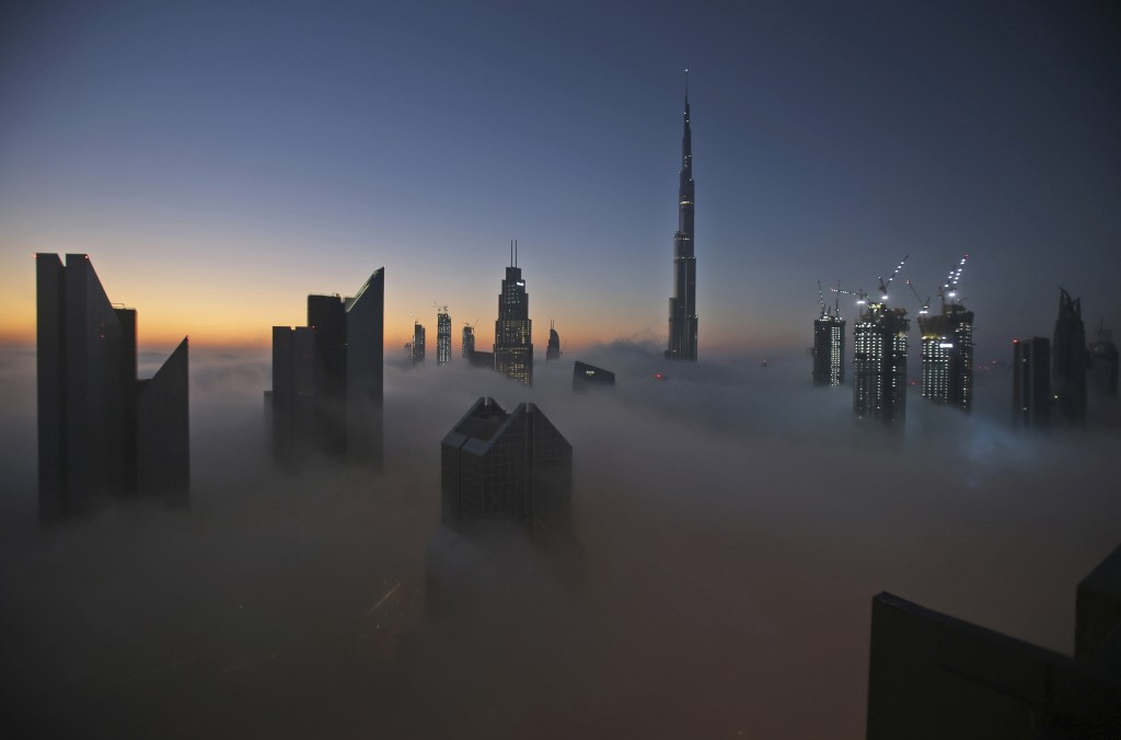 FILE - In this Dec. 31, 2016 file photo, the sun rises over the city skyline with the Burj Khalifa, the world's tallest building, on a foggy day in Du...