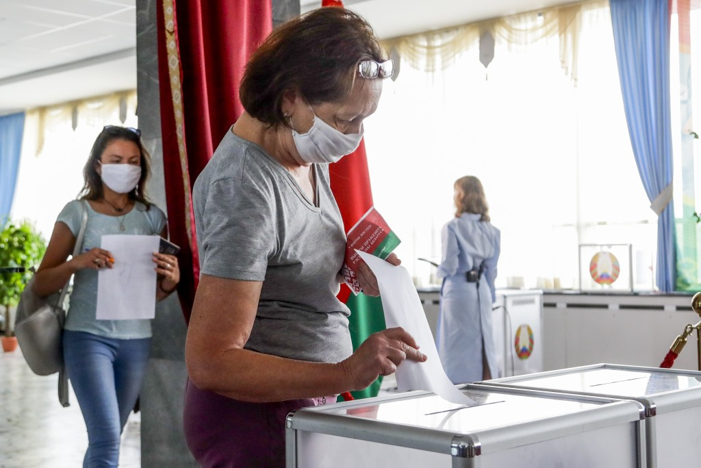 FILE - In this Aug. 9, 2020, file photo, a woman casts her ballot at a polling station during the presidential election in Minsk, Belarus, Sunday, Aug...