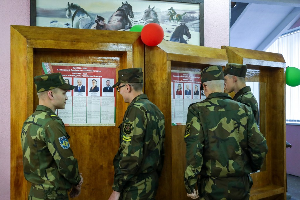 FILE - In this Aug. 9, 2020, file photo, Belarusian soldiers read about the candidates before voting at a polling station during the presidential elec...