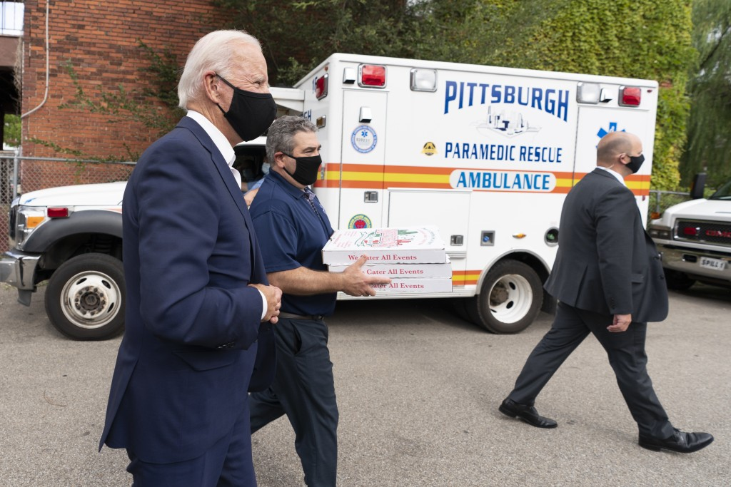 Democratic presidential candidate former Vice President Joe Biden arrives with pizza as he visits Pittsburgh Local Fire Fighters No. 1 in Pittsburgh, ...