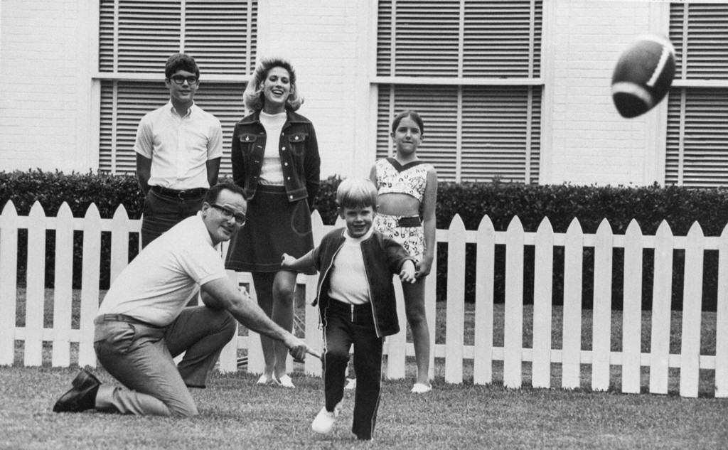 FILE - In this June 1, 1970, file photo, Kansas City Chiefs owner Lamar Hunt watches after holding the ball for his son, Clark, 5, to kick in the fami...