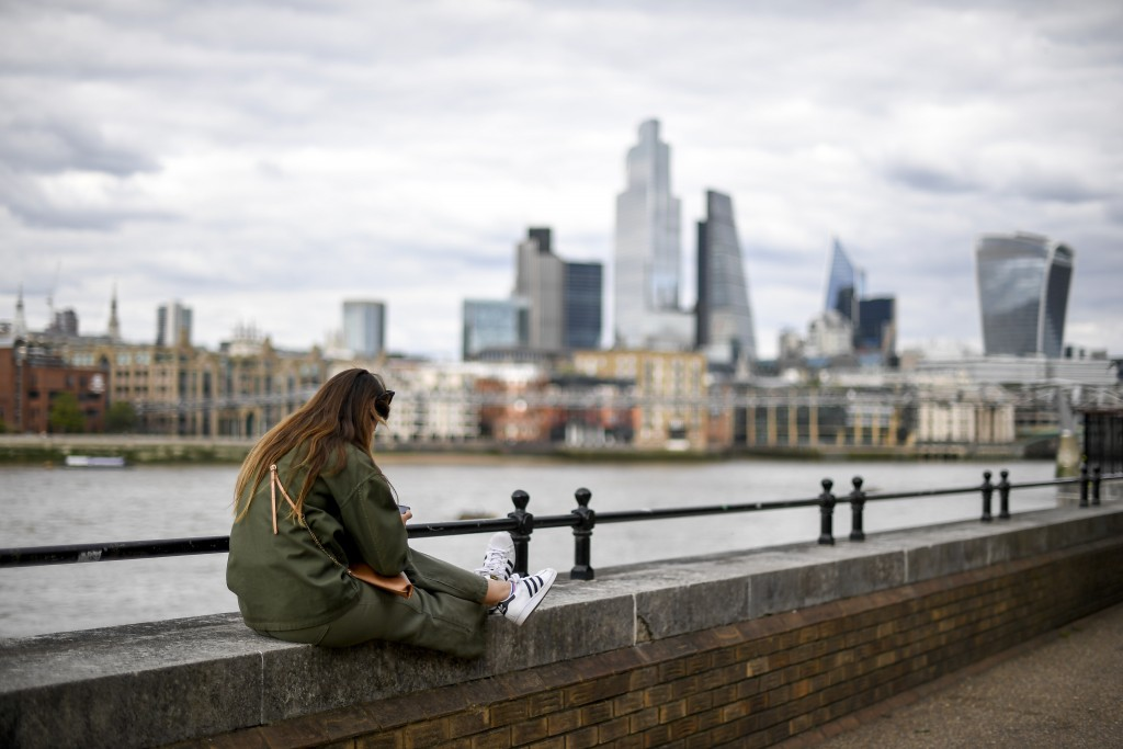 A woman sits on the edge of the south bank of the river Thames, in London, Monday, Aug. 31, 2020. Today is the last day of the 'Eat out to help out' s...