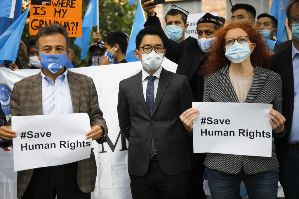 Hong Kong activist Nathan Law, center, takes part in a protest during the visit of Chinese Foreign Minister Wang Yi in Berlin, Germany, Tuesday, Sept....