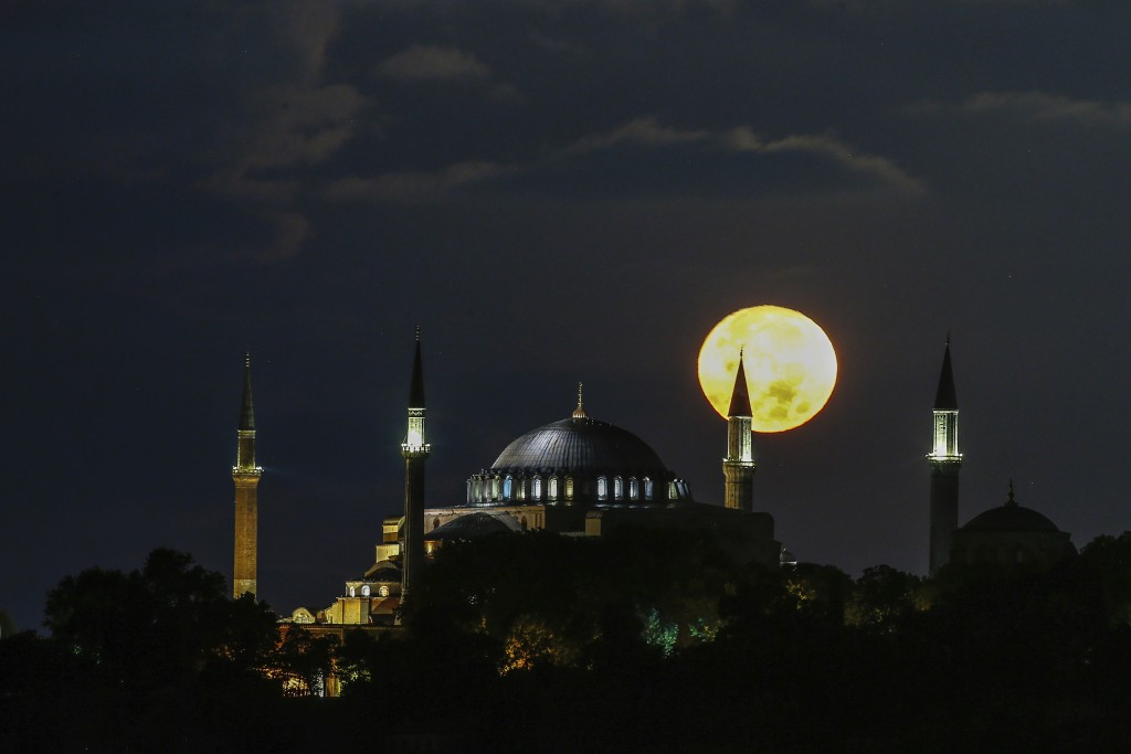 The full moon rises behind the Byzantine-era Hagia Sophia in the historic Sultanahmet district of Istanbul, early Tuesday, Sept. 1, 2020. Worshipers h...