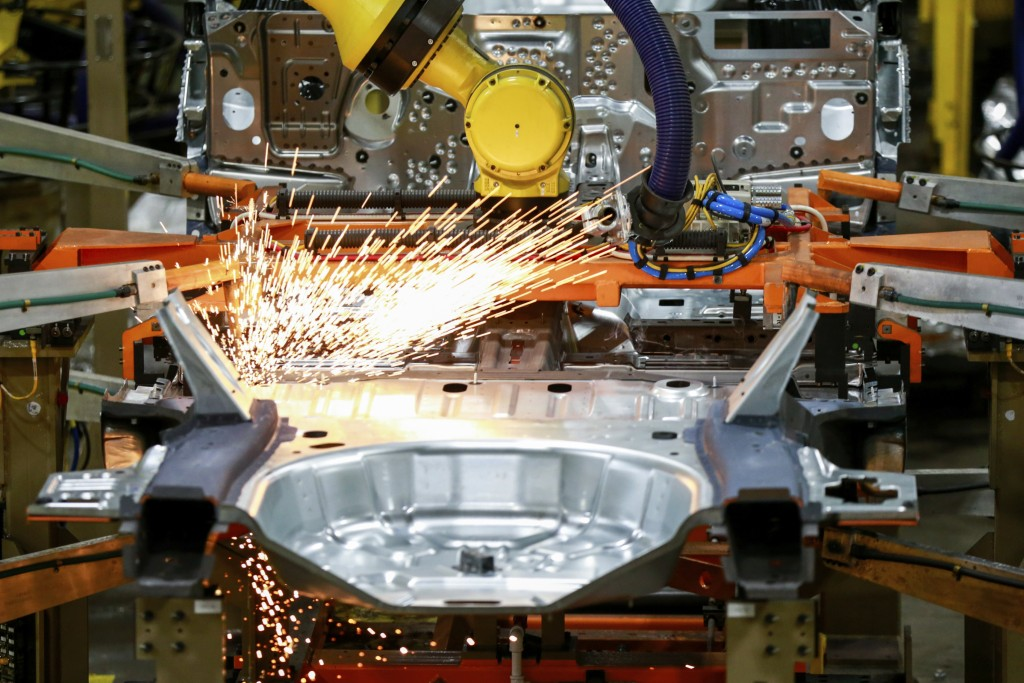 FILE - In this June 24, 2019, file photo machines work on a Ford vehicle assembly line at Ford's Chicago Assembly Plant in Chicago.  American factorie...