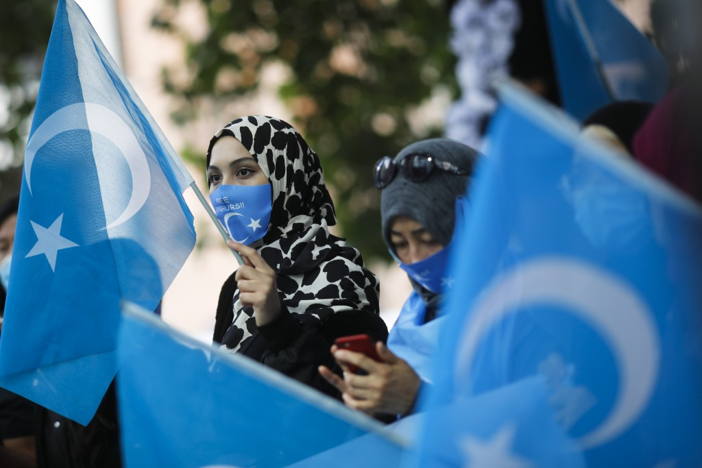 Uyghurs women take part in a protest during the visit of Chinese Foreign Minister Wang Yi in Berlin, Germany, Tuesday, Sept. 1, 2020. German Foreign M...
