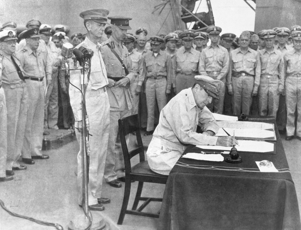FILE- In this Sept. 2, 1945, file photo, U.S. Gen. Douglas MacArthur signs the Japanese surrender documents, aboard the USS Missouri in Tokyo Bay, for...