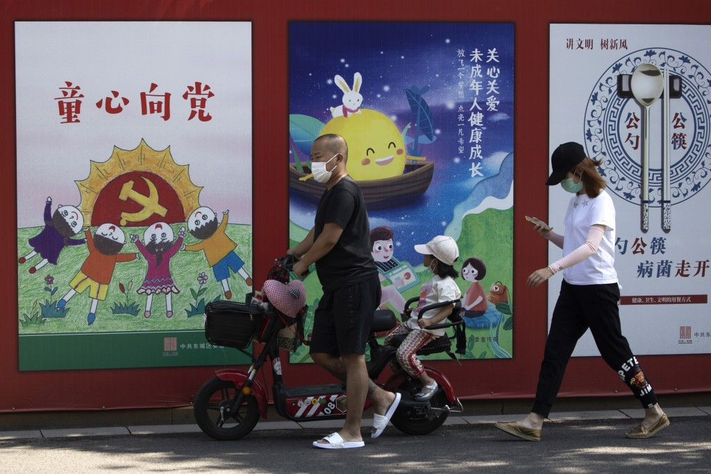 "A man wearing a mask to protect from the coronavirus pushes an electric bike with a child past propaganda posters with the words ""Childlike devotion t..."