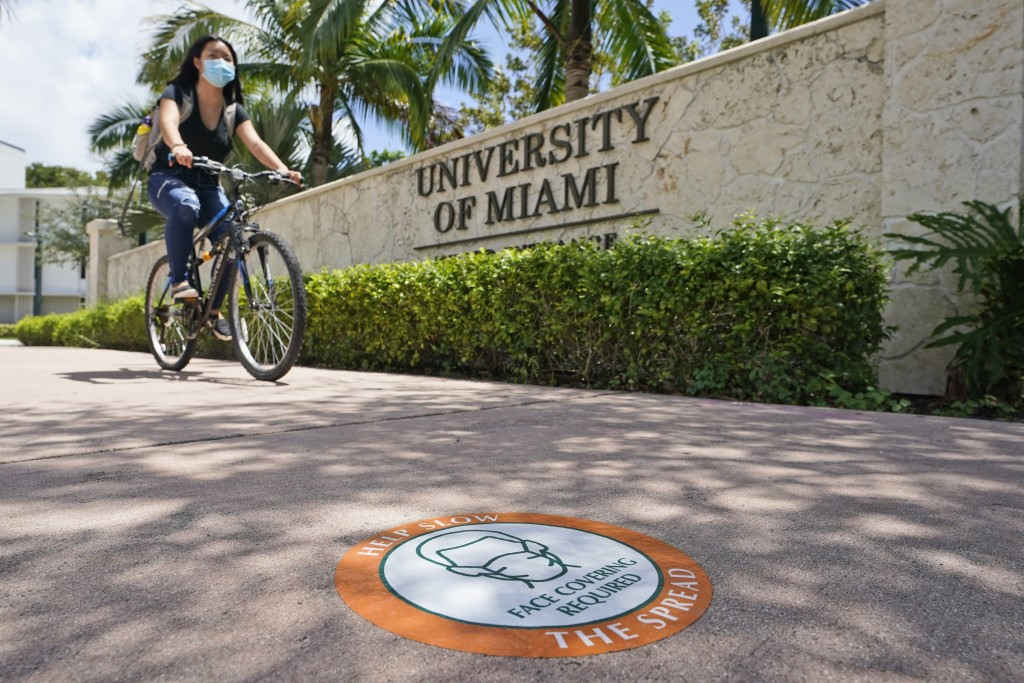 FILE - In this Aug. 25, 2020, file photo, a cyclist, wearing a mask to prevent the spread of the new coronavirus, rides by an entrance to the Universi...
