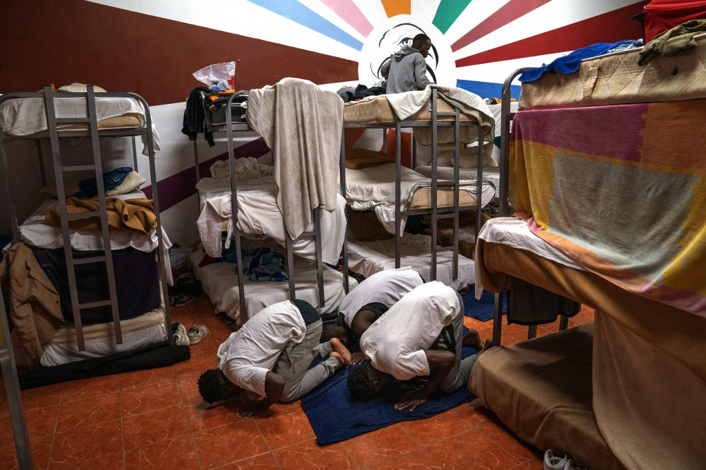 Asylum-seekers pray next to their beds at the Modern Christian Mission Church in Fuerteventura, one of the Canary Islands, Spain, on Saturday, Aug. 22...