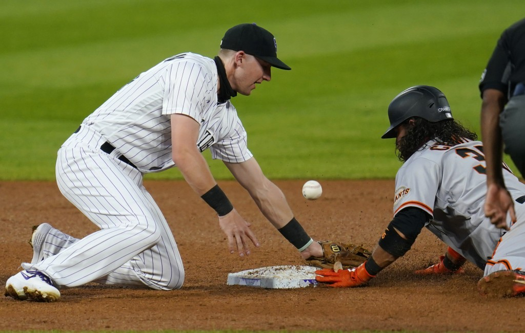 Colorado Rockies second baseman Ryan McMahon, left, bobbles the pickoff throw as San Francisco Giants' Brandon Crawford steals second base in the thir...