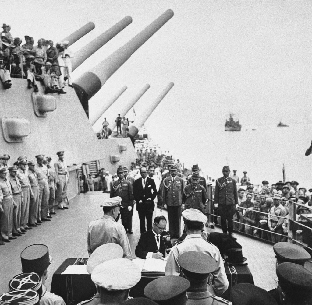 FILE- In this Sept. 2, 1945, file photo, Japanese Foreign Minister Mamoru Shigemitsu signs Japanese Instrument of Surrender, a document signed on the ...