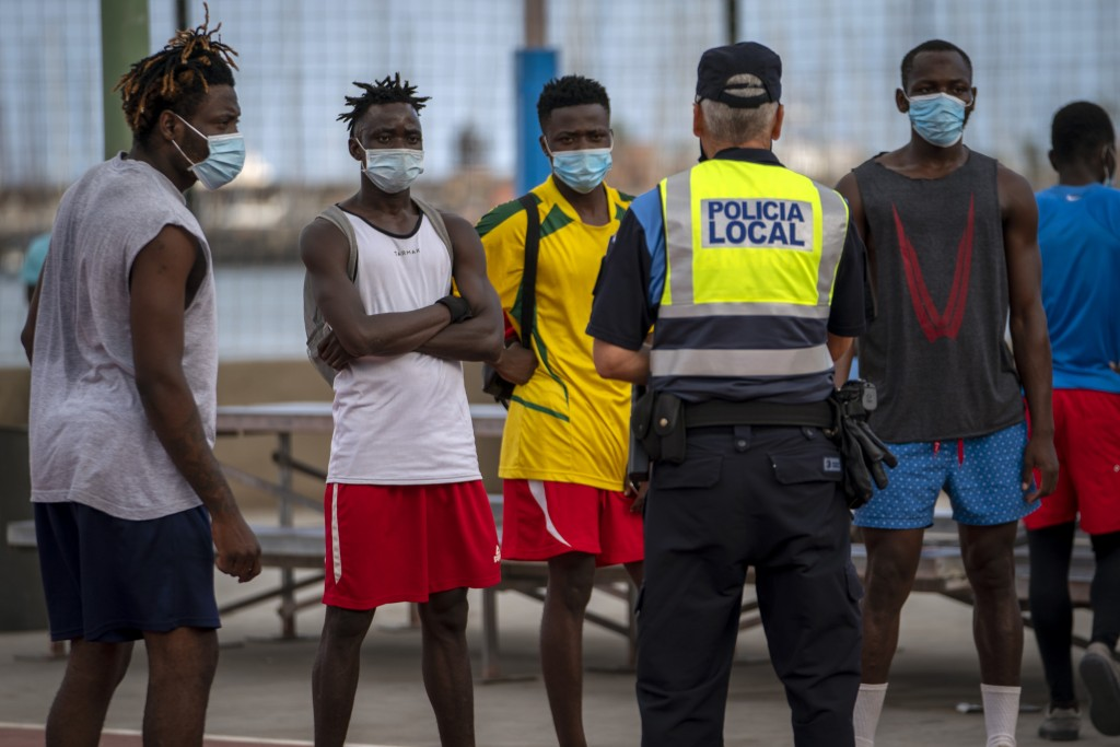 A police officer tells migrants and asylum-seekers to stop playing soccer due to coronavirus restrictions on contact sports in Gran Canaria island, Sp...