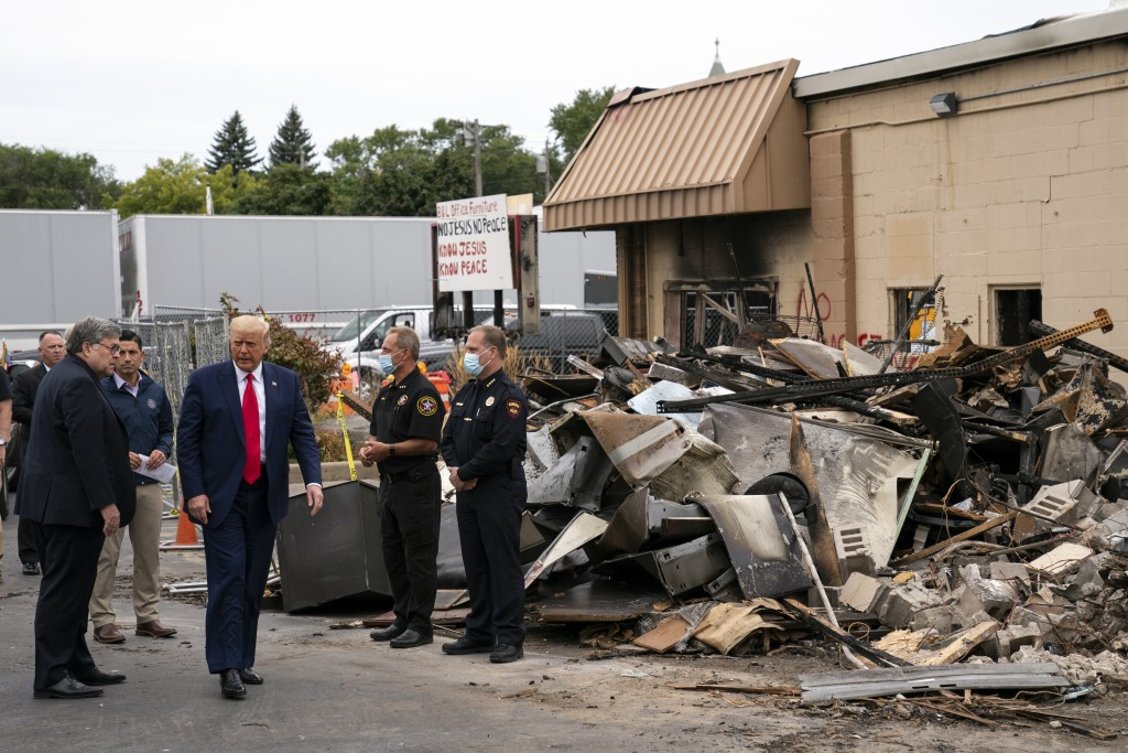 President Donald Trump walks Tuesday, Sept. 1, 2020, as he tours an area damaged during demonstrations after a police officer shot Jacob Blake in Keno...