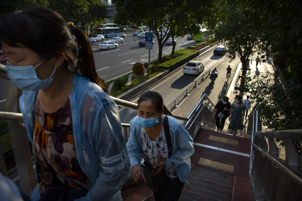 People wearing face masks to protect against the coronavirus walk along a pedestrian overpass in the central business district in Beijing, Wednesday, ...