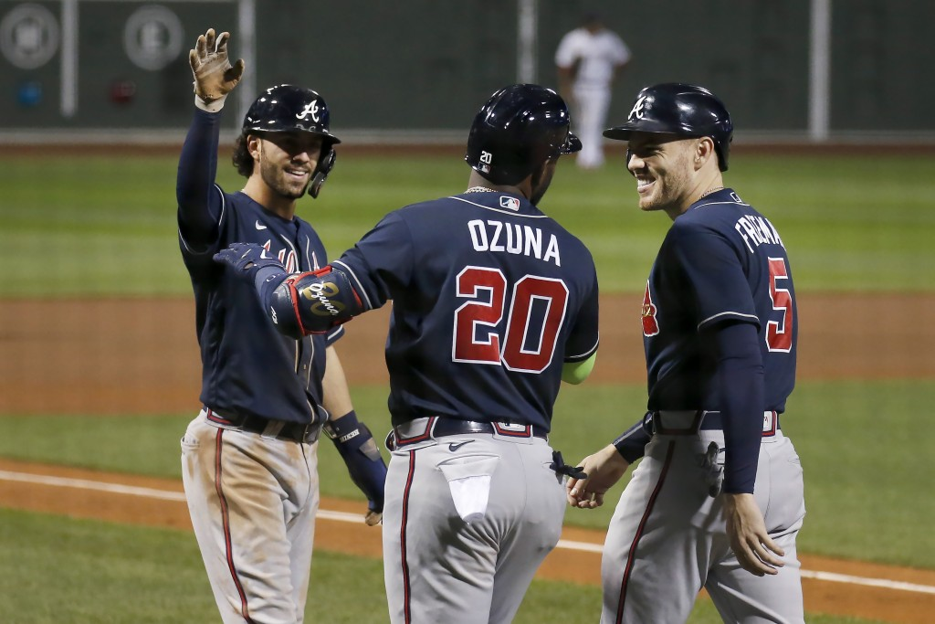 Atlanta Braves' Marcell Ozuna (20) celebrates with teammates Dansby Swanson, left, and Freddie Freeman (5) after they all scored on Ozuna's three-run ...