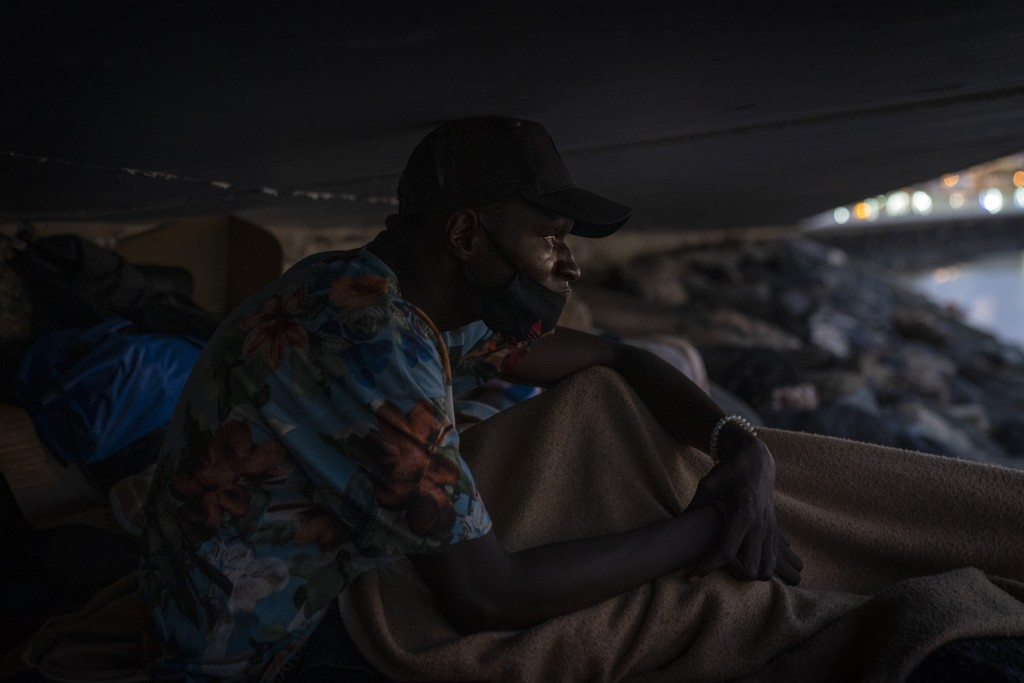 Khalid, a migrant from Gambia, sits on a breakwater under a bridge in Gran Canaria island, Spain, on Saturday, Aug. 22, 2020. More than 250 people are...