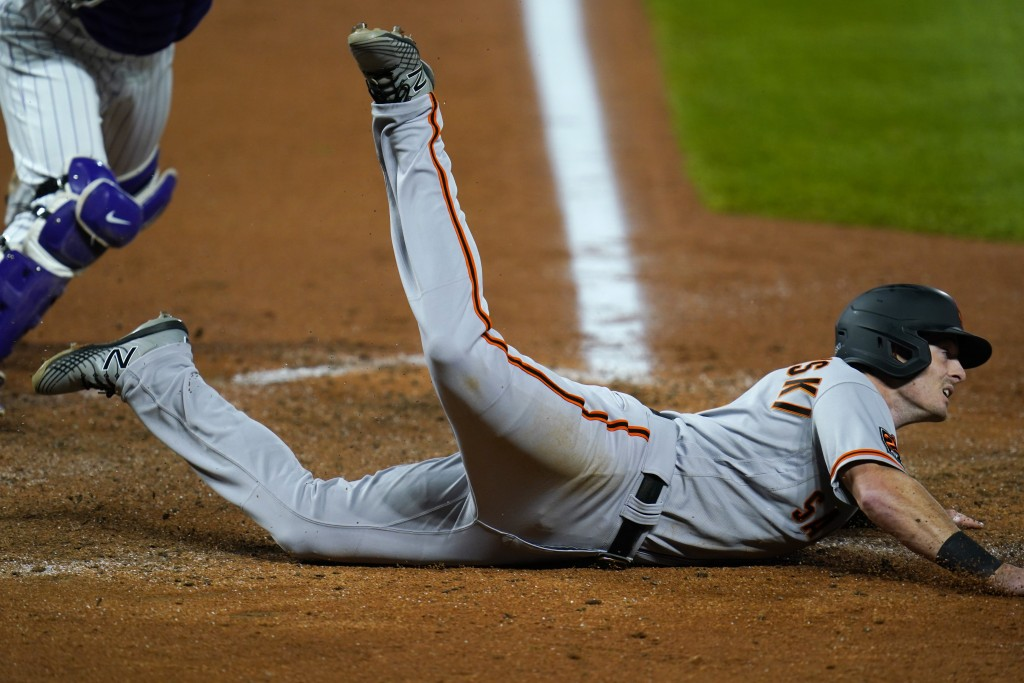 San Francisco Giants' Mike Yastrzemski tumbles past home plate after he was tagged out while trying to score on a double hit by Alex Dickerson in the ...