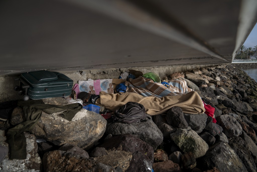 Khalid, a migrant from Gambia, sleeps on a breakwater under a bridge in Gran Canaria island, Spain, on Saturday, Aug. 22, 2020. The striking shift in ...