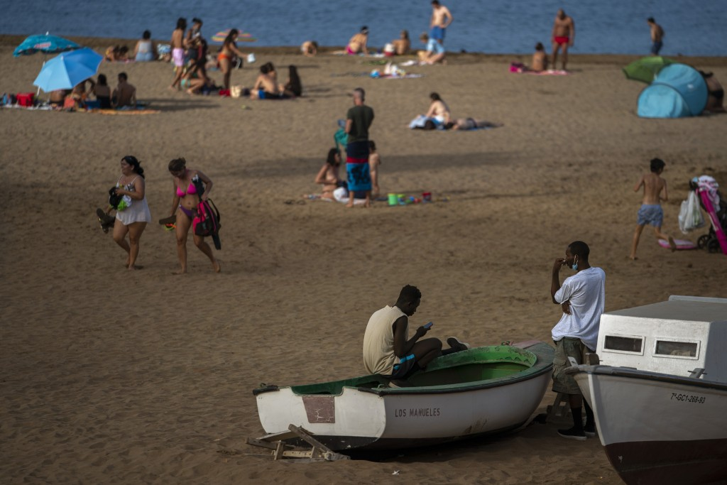 Two migrants sit on a fishing boat as people enjoy the beach in Gran Canaria island, Spain, on Friday, Aug. 21, 2020. Though migrant arrivals to mainl...