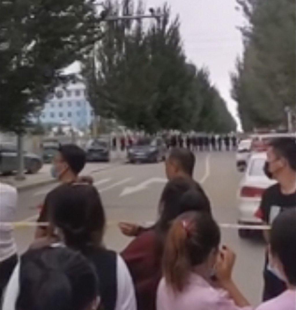 In this image made from video taken in August 2020, parents gather behind a police line outside a school in Tongliao in Northwestern China's Inner Mon...