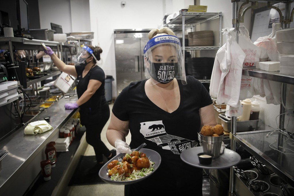 FILE - In this July 1, 2020, file photo, a waitress takes a food order from the kitchen at Slater's 50/50 in Santa Clarita, Calif. Gov. The torrid cor...