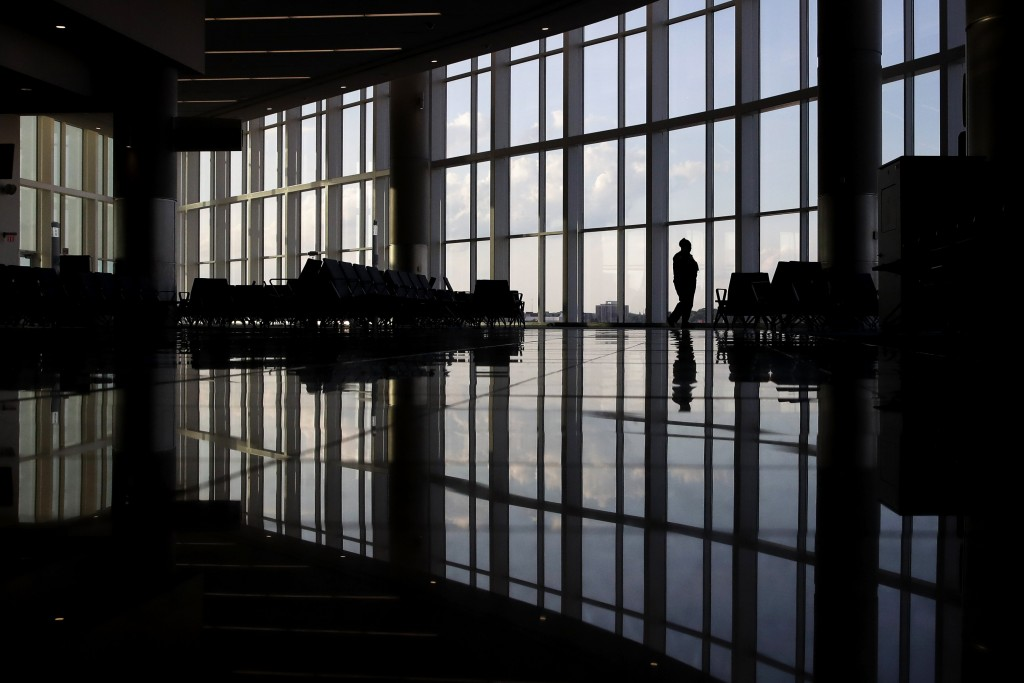 FILE - In this Monday, June 1, 2020 file photo, a woman looks through a window at a near-empty terminal at an airport in Atlanta. Anxiety and depressi...