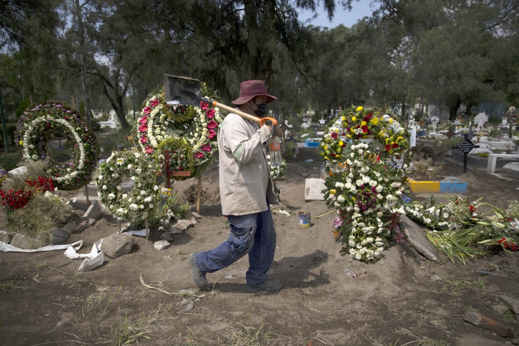 A grave digger walks in the COVID-19 section of the cemetery of San Lorenzo Tezonco Iztapalapa on the outskirts of Mexico City, Tuesday, Sept. 1, 2020...