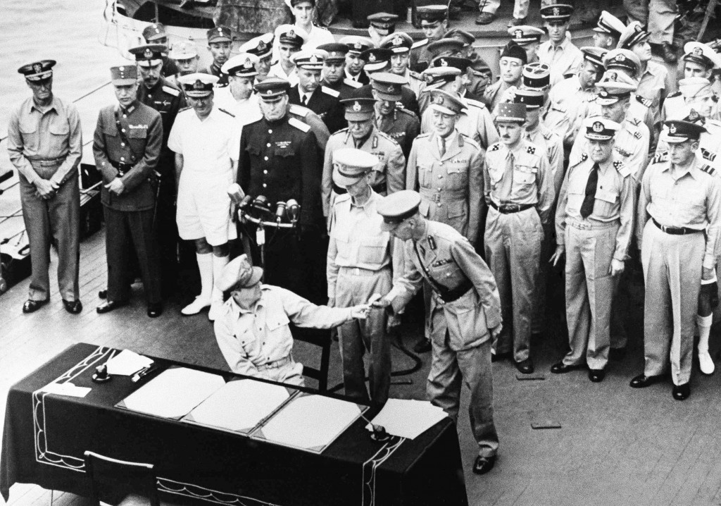 FILE - In this Sept. 2, 1945, file photo, U.S. General Douglas MacArthur hands the pen to British Lieut. Gen. Arthur E. Percival after signing surrend...